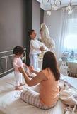 Zrelaksowana matka i synowie bawić się nad łóżkiem zdjęcie stock
