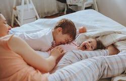 Zrelaksowana matka i synowie bawić się nad łóżkiem fotografia royalty free