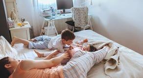 Zrelaksowana matka i synowie bawić się nad łóżkiem obrazy stock