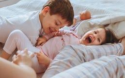 Zrelaksowana matka i synowie bawić się nad łóżkiem fotografia stock