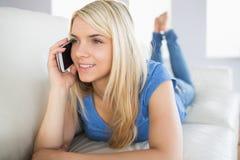 Zrelaksowana piękna kobieta używa telefon komórkowego w żywym pokoju Zdjęcia Stock