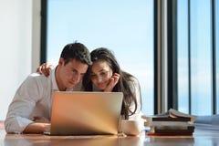 Zrelaksowana potomstwo para pracuje na laptopie w domu Fotografia Stock