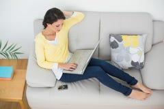 Zrelaksowana przypadkowa brunetka w żółtym kardiganie pisać na maszynie na laptopie Fotografia Royalty Free