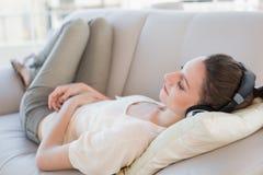 Zrelaksowana przypadkowa młoda kobieta cieszy się muzykę na kanapie zdjęcia stock