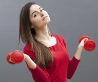 Zrelaksowana 20s biurowa dziewczyna trzyma niemych dzwony dla stonowanych ręk i wellness Obraz Stock