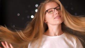 Zrelaksowana szczęśliwa blondynka obraca jej chodzenie i włosy podczas gdy patrzejący kamerę w szkłach i pokazywać artystyczny sz