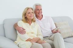 Zrelaksowana szczęśliwa starsza para z pilot do tv Obrazy Stock