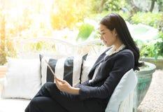 Zrelaksowana uśmiechnięta kobieta używa cyfrową pastylkę w żywym pokoju Zdjęcia Royalty Free