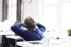 Zrelaksowanego Afro biznesowego mężczyzna Amerykański obsiadanie przy jego biurkiem patrzeje w powietrze Zdjęcie Royalty Free