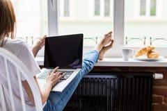Zrelaksowanej młodej kobiety pracujący laptop z nogami na widnowsill z ranku śniadaniem zdjęcia stock