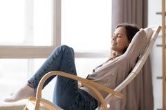Zrelaksowanej spokojnej młodej kobiety lounging siedzieć w wygodnym kołysa krześle obrazy royalty free