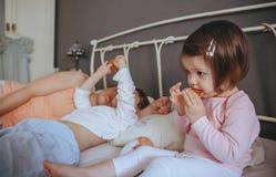 Zrelaksowani małej dziewczynki łasowania ciastka nad łóżkiem Fotografia Stock