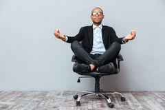 Zrelaksowany afrykański młodego człowieka obsiadanie i medytować na biurowym krześle Fotografia Stock