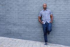 Zrelaksowany amerykanina afrykańskiego pochodzenia mężczyzna opiera przeciw ścianie Zdjęcie Royalty Free