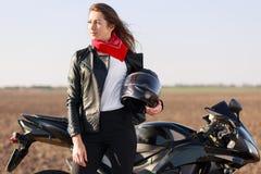 Zrelaksowany beztroski żeński rowerzysta patrzeje zamyślenie na boku, niesie hełm, ubierającego w czarnej skórzanej kurtce blisko obraz royalty free