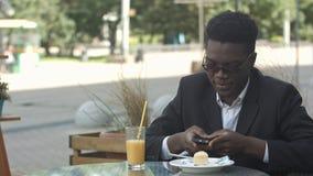 Zrelaksowany beztroski młody afro amerykański mężczyzna siedzi samotnie przy kawiarnia stołem w eleganckim eyewear, używać mądrze Zdjęcie Stock
