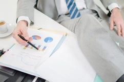 Zrelaksowany biznesmen sprawdza pieniężnych wykresy Obrazy Royalty Free
