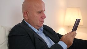 Zrelaksowany biznesmena obsiadanie na kanapie Używa telefonu komórkowego i napoju alkohol zdjęcie wideo
