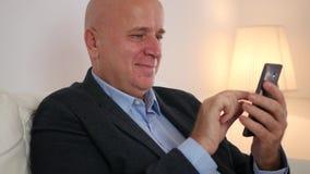 Zrelaksowany biznesmena pobyt w kanapa tekscie i uśmiechu Używać telefon komórkowego zbiory wideo