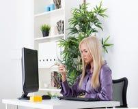 Zrelaksowany bizneswomanu wysylanie sms w jaskrawym biurze Obrazy Royalty Free