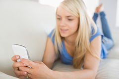 Zrelaksowany kobiety wysylanie sms w żywym pokoju Fotografia Royalty Free