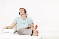 Zrelaksowany mężczyzna słucha muzyka z słuchawkami i oczami zamykającymi. Obraz Stock