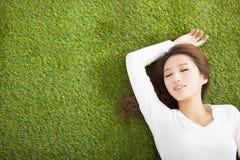 Zrelaksowany młodej kobiety lying on the beach na trawie zdjęcia royalty free