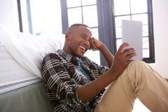 Zrelaksowany młody afro amerykański facet używa cyfrową pastylkę w domu Obraz Stock