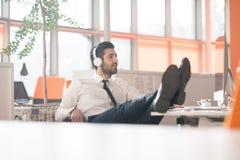 Zrelaksowany młody biznesowy mężczyzna przy biurem Zdjęcie Stock