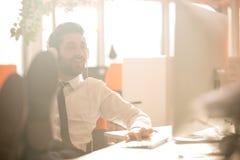 Zrelaksowany młody biznesowy mężczyzna przy biurem Obrazy Stock