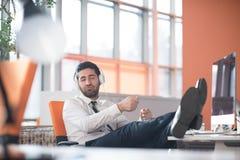 Zrelaksowany młody biznesowy mężczyzna przy biurem Zdjęcia Stock
