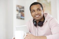 Zrelaksowany młody człowiek z cyfrowym touchpad Zdjęcia Royalty Free
