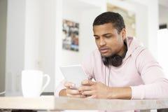 Zrelaksowany młody człowiek z cyfrowym touchpad Obrazy Royalty Free
