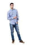 Zrelaksowany młody korporacyjny mężczyzna mienia telefon komórkowy patrzeje kamerę zdjęcia stock