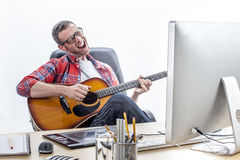 Zrelaksowany przedsiębiorcy śpiew i bawić się przy ministerstwa spraw wewnętrznych biurkiem gitara Obraz Royalty Free