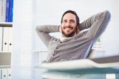 Zrelaksowany przypadkowy biznesmen oparty przy jego biurkiem z powrotem obrazy stock