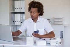 Zrelaksowany przypadkowy biznesmen robi zakupy online przy jego biurkiem fotografia stock