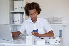 Zrelaksowany przypadkowy biznesmen robi zakupy online przy jego biurkiem obraz stock