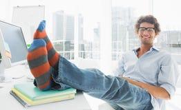 Zrelaksowany przypadkowy mężczyzna z nogami na biurku w biurze zdjęcie stock