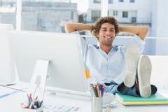 Zrelaksowany przypadkowy mężczyzna z nogami na biurku w jaskrawym biurze fotografia stock