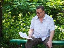 Zrelaksowany przypadkowy obsiadanie mężczyzna czytanie i Obrazy Stock