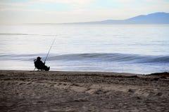 Zrelaksowany rybaka połów na plaży Fotografia Royalty Free