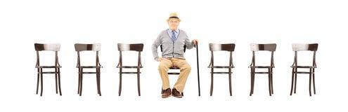 Zrelaksowany starszy dżentelmenu obsiadanie na drewnianym krześle Obraz Stock