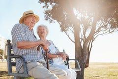 Zrelaksowany starszy pary obsiadanie na parkowej ławce fotografia royalty free