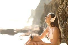 Zrelaksowany sunbather słucha muzyka na plaży obrazy royalty free