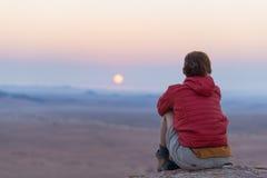 Zrelaksowany turystyczny obsiadanie na skałach i patrzeć zmierzch w Namib pustyni, najlepszy podróży miejsce przeznaczenia w Nami Zdjęcie Stock