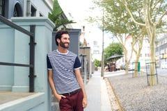 Zrelaksowany uśmiechnięty mężczyzna opiera na ścianie outdoors Obraz Royalty Free