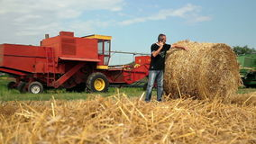 Zrenjanin, SERBIA- August 2013:  Wheat Harvest. Farmer with cell phone checking the fresh hay bale during wheat harvest on avgust 2013 in Zrenjanin. HD1080p stock video