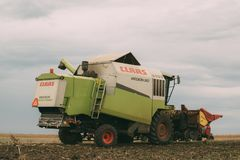 Combine harvester unloading harvested corn into tractor trailer Stock Photo