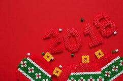 2018 zrobili od mini paciorkowatego ornamentu odizolowywającego na czerwonym tle z przestrzenią dla teksta Zdjęcie Royalty Free